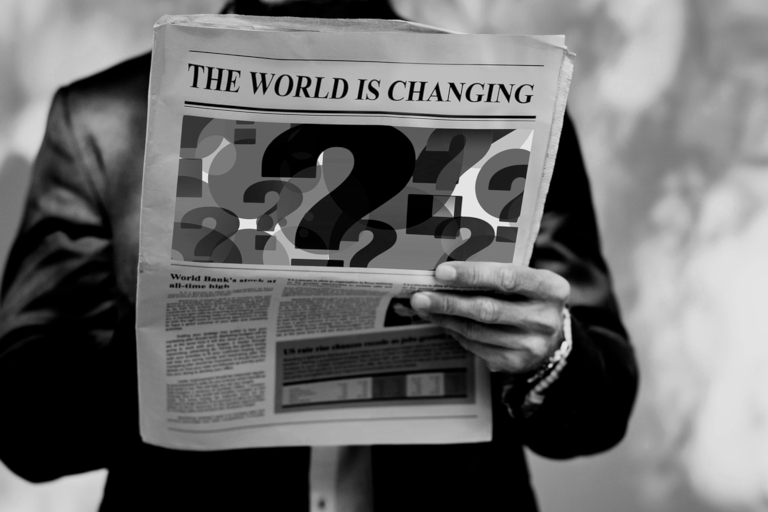 """photo un homme lit un journal affichant """"the world is changing"""""""